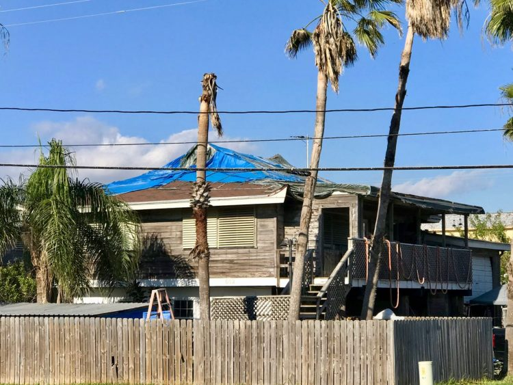 House with blue tarps on roof